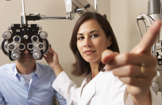 Female Optician In Surgery Giving Man Eye Test